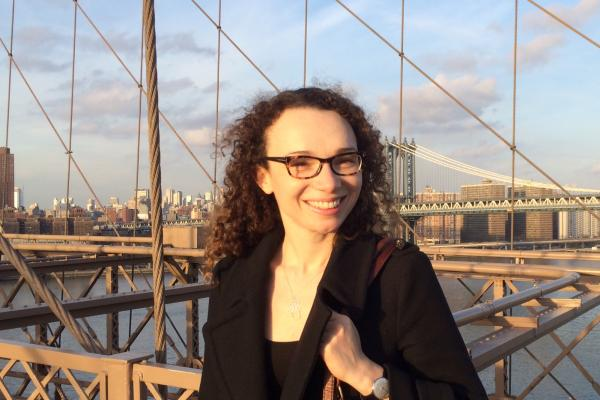 Cecile Bishop, who has long dark hair and wears glasses, standing on a bridge