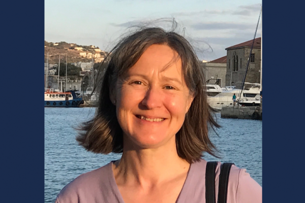 Professor Teresa Morgan standing in a harbour with boats in the background