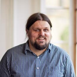 A man with long dark hair in a ponytail and a beard wearing a blue and white shirt