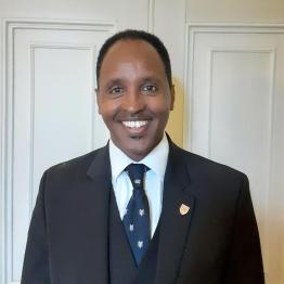 Asefay Aberaha, who has short black hair and is wearing a suit and tie