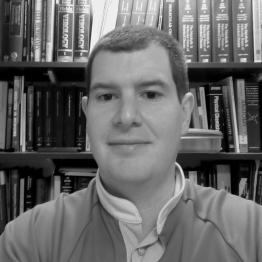 Black and white photo of a man with short dark hair standing in front of a bookshelf