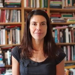 Dr Guadalupe Gerardi standing in a book lined study
