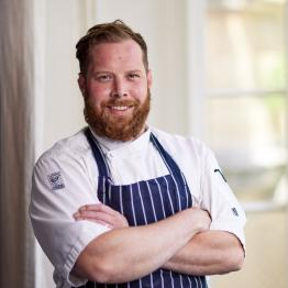 A man with short auburn hair and a beard wearing chefs whites and a blue apron