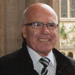 A man with very short grey hair and glasses wearing a white shirt and dark jacket