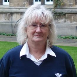 A woman with chin-length grey hair with glasses wearing a white shirt and dark jumper