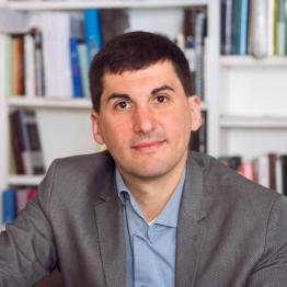 A man with short dark hair and a grey suit sitting in front of a bookshelf