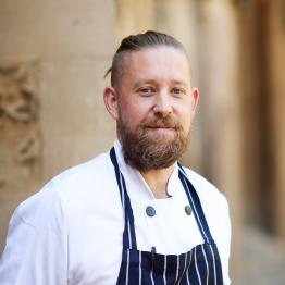A man with tied-back brown hair and a beard wearing chef's whites and a striped apron