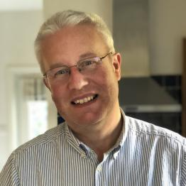 A man with short grey hair and glasses wearing a striped blue shirt