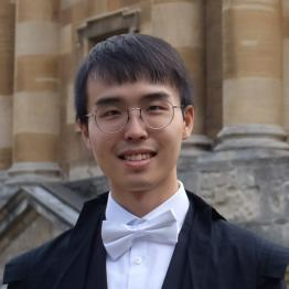 A man with short dark hair and round glasses wearing academic dress