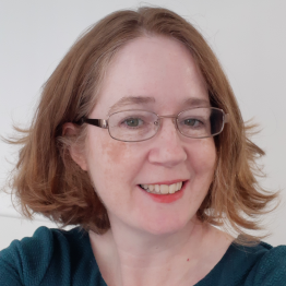 A woman with short auburn hair and glasses