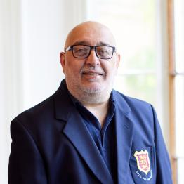 A man with glasses and a grey beard wearing a navy blazer