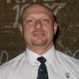 A man with a bald head wearing a white shirt and dark tie