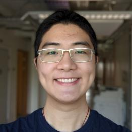 A smiling man with short dark hair and glasses