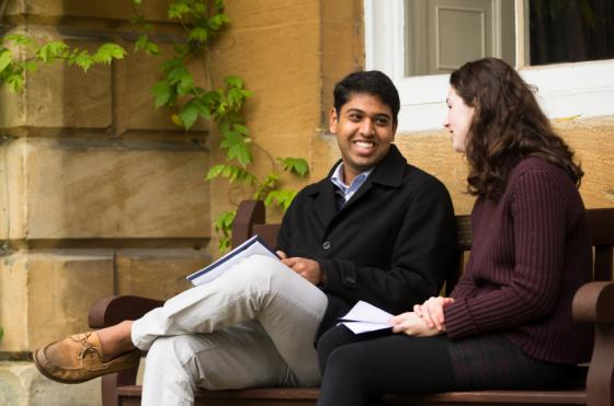 Two students sitting on a bench chatting
