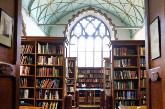 Image of the inside of Oriel Library with a large window and rows of books