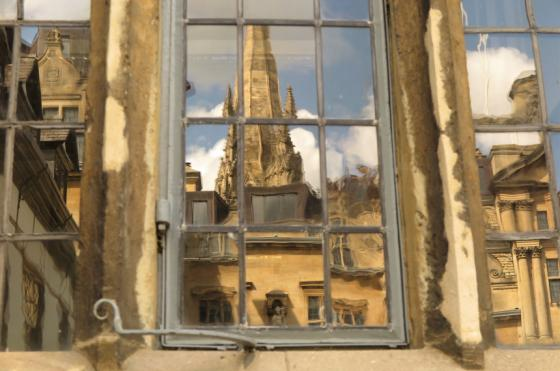 A reflection of the spire of University Church in Oxford from the window of Oriel College