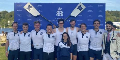 Nine men and one woman, wearing blue shorts and white tops posing in front of two crossed oars with tortoises on