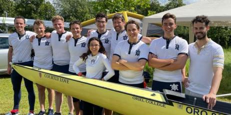 Nine men and one woman, wearing blue shorts and white tops posing with a yellow rowing boat