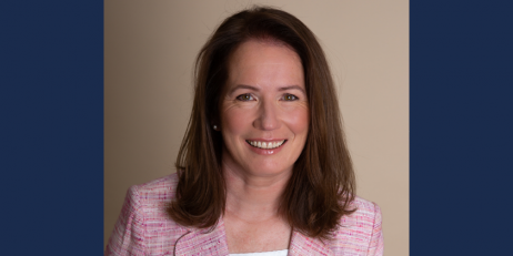 A smiling woman with long brown hair wearing a pink suit
