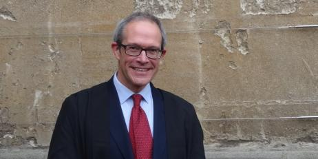 Professor Mark Wynn wearing academic dress in front of a stone wall