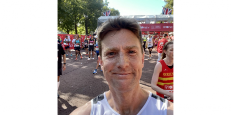 A man with short dark hair and freckles crossing the finish line of the London Marathon