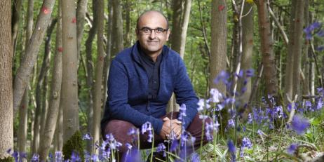 Professor Yadvinder Malhi in Wytham Woods, surrounded by trees and bluebells