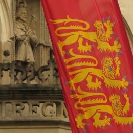 A close-up of a red flag with three yellow lions on it in front of Oriel's Hall steps